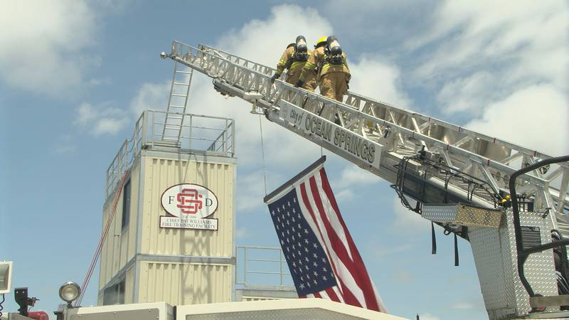 Ocean Springs firefighters climb a ladder to the roof of the Chief Pat Williams Training...