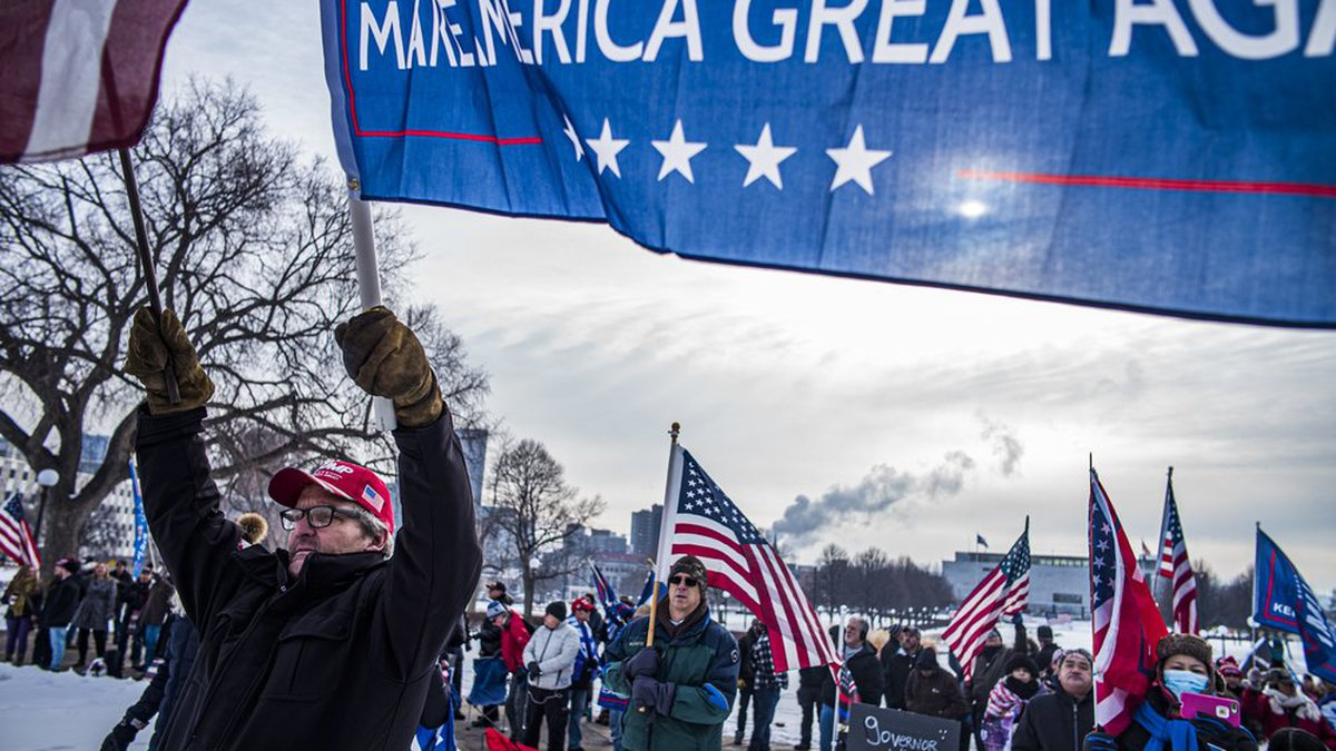 Gerald Williams holds a banner during a rally in support of President Donald Trump on the steps...
