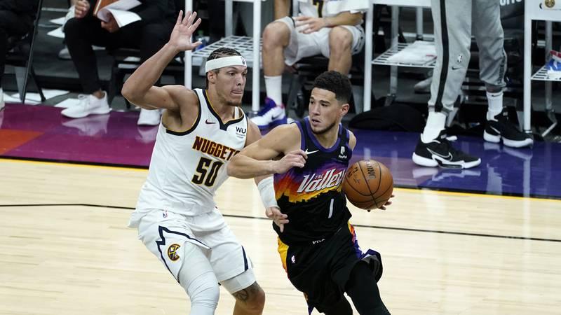 Phoenix Suns guard Devin Booker (1) drives as Denver Nuggets forward Aaron Gordon (50) defends...