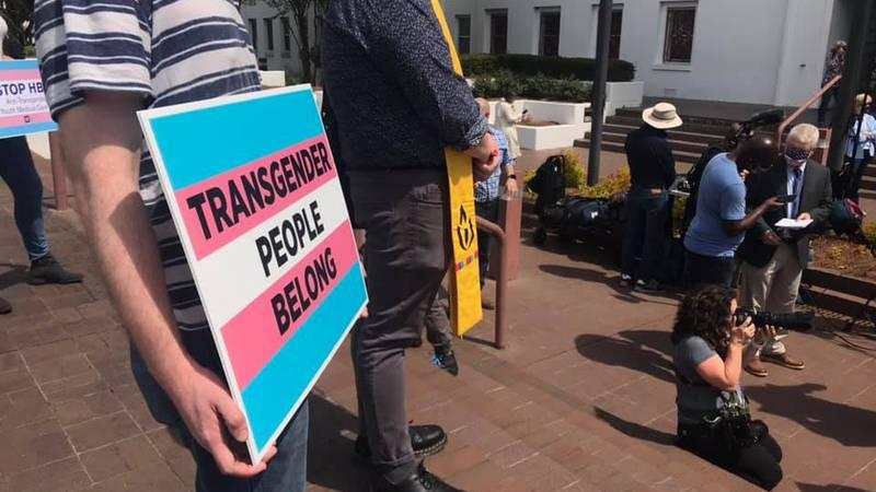 Protesters rally outside statehouse against transgender bills.