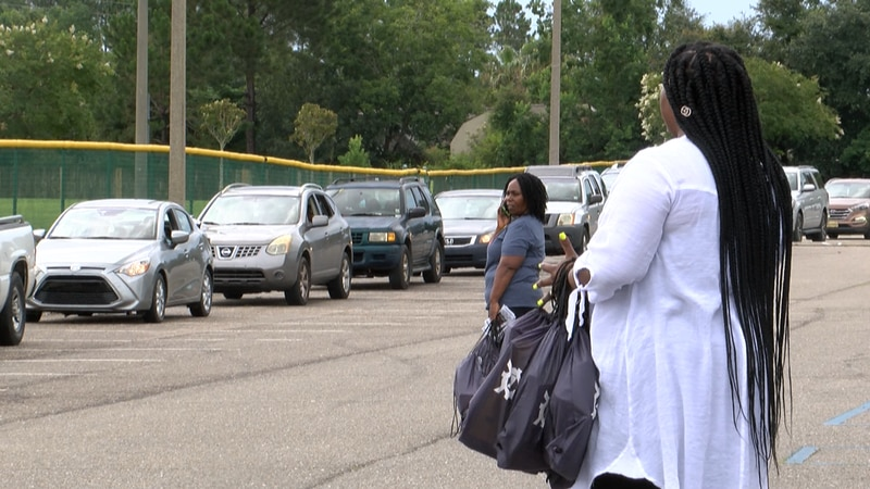 Volunteers stuffed backpacks with school supplies to give out to parents as they arrived at...