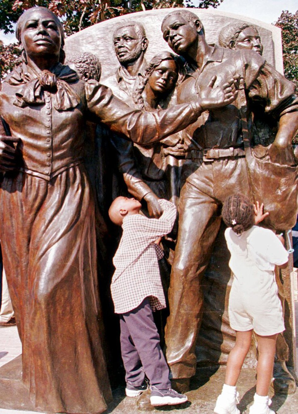 Byusa Kironyo, 7, and his sister, Bwiza Kironyo, 5, both of Brockton, Mass., explore a statue...
