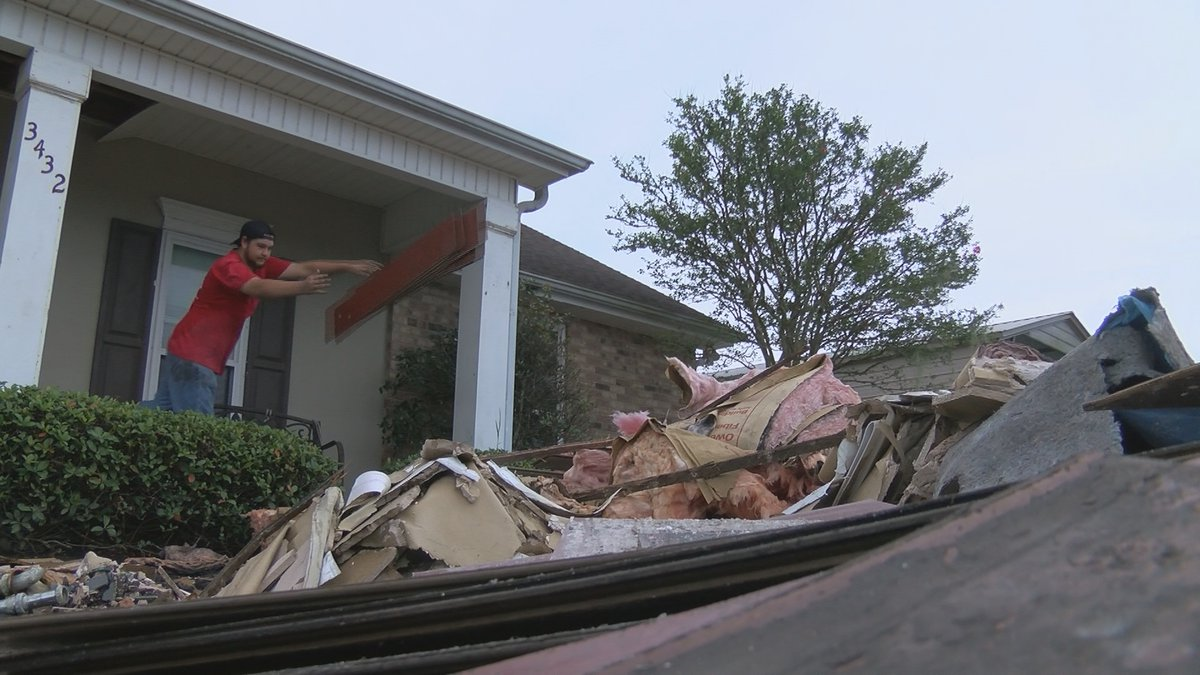 Kade Vincent tossing out flooring out of his Jean Lafitte home into a pile of debris.