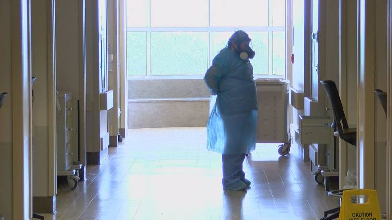 A nurse puts on PPE before entering a room on the COVID wing at Memorial Hospital at Gulfport.