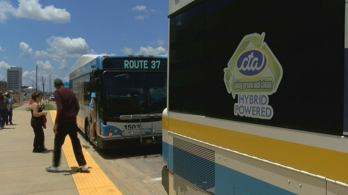 Riders board one of Coast Transit Authority's electric-diesel hybrid buses at the Gulfport...