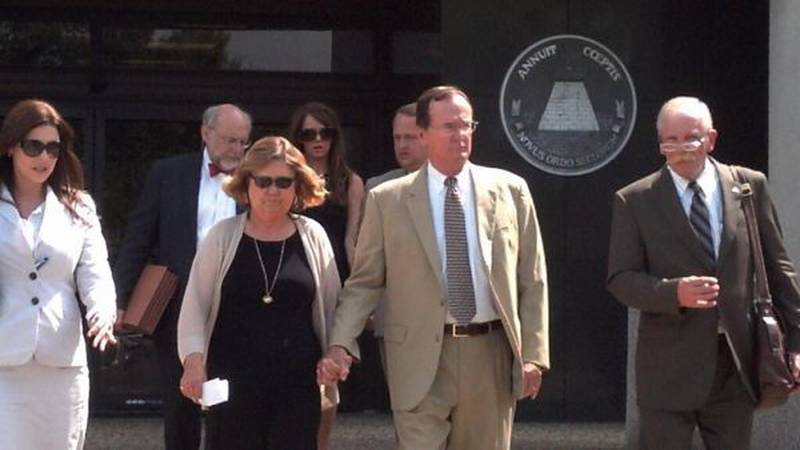 Dr. Bill Walker left the courthouse holding hands with his wife, Sharon, and followed by his...