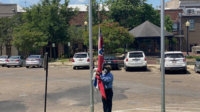 A city worker removes the Mississippi state flag from Laurel City Hall.