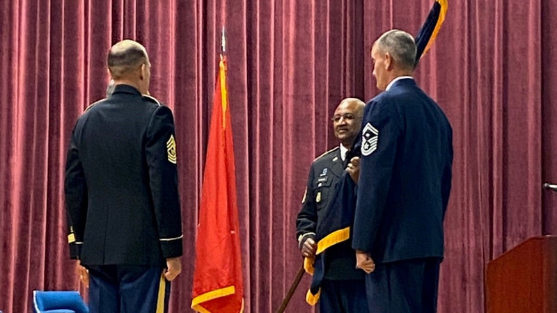 Sgt. Maj. Silvester Tatum holds flag to symbolize the change of responsibility.