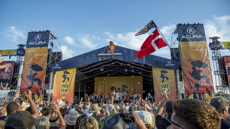 FILE - Festival goers attend the New Orleans Jazz and Heritage Festival in New Orleans on April...