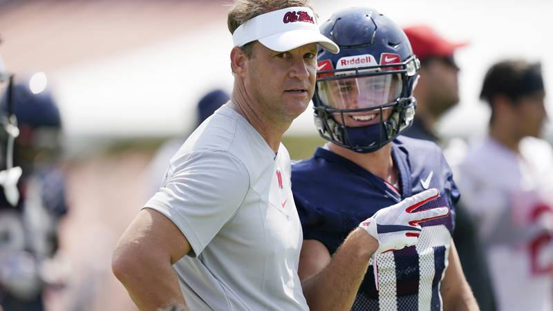 Mississippi football coach Lane Kiffin, left, and wide receiver John Rhys Plumlee (10) look at...