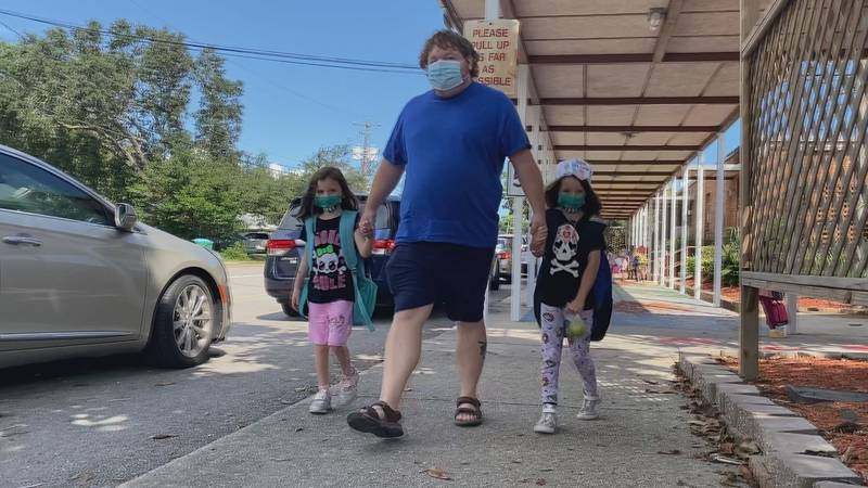 Justin Peters of Gulfport walks his children to their car after school on Monday.