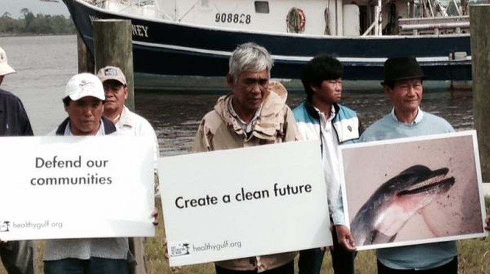 Against a backdrop of shrimp boats, Vietnamese fishermen held message boards, along with...