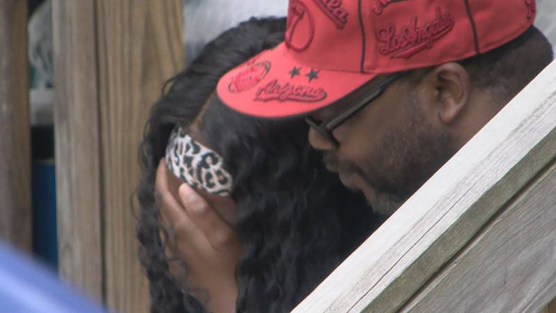 Tyrone Powell's brother, Frederick Powell, consoles Tyrone's daughter, Tyneshia Powell.