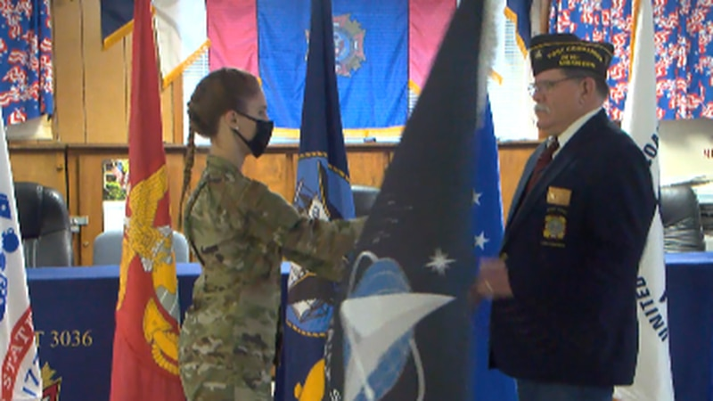 Cadet Colonel Emily Riter, a senior in ROTC at USM presents a Space Force Flag to Commander...