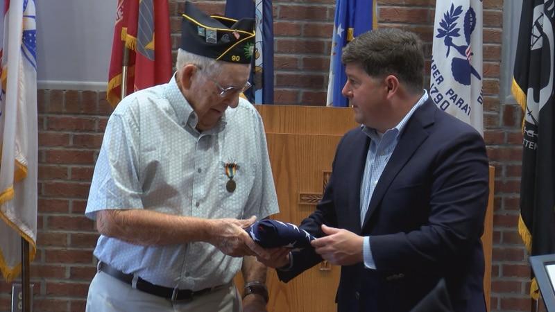 Rep. Steven Palazzo presents an American flag to World War Two veteran Henry Bennett Thursday...