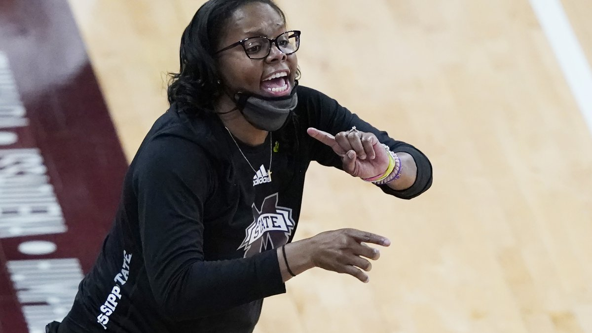 Mississippi State coach Nikki McCray-Penson lowers her mask as she calls to players during the...