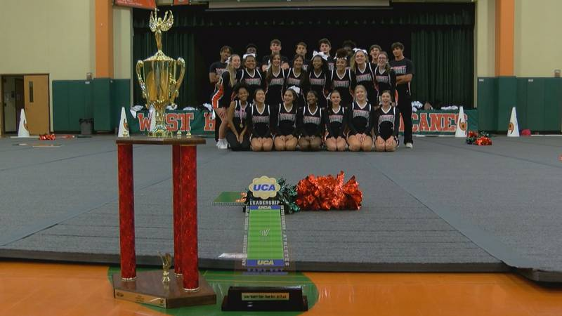 The West Harrison High School cheer squad pose with their state and national trophies.