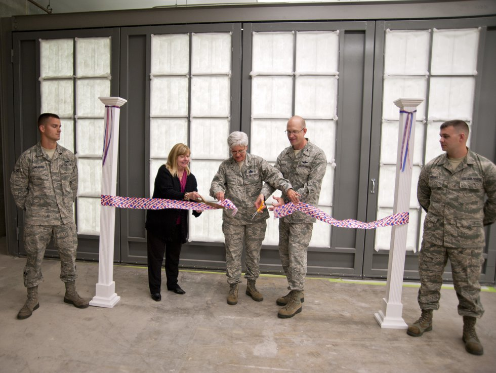 Col. Jay Jensen, Col. Anna Schulte and Hermis Plash cut the ceremonial ribbon to open the new...