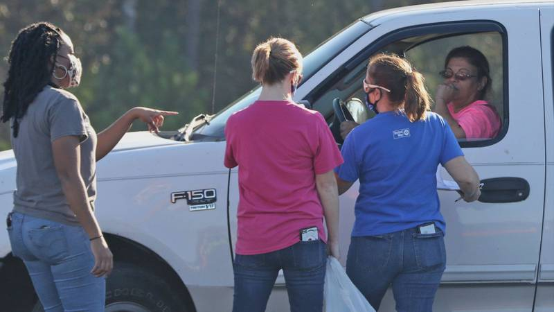 Volunteers talk to a recipient during a mobile pantry sponsored by Feeding the Gulf Coast at...