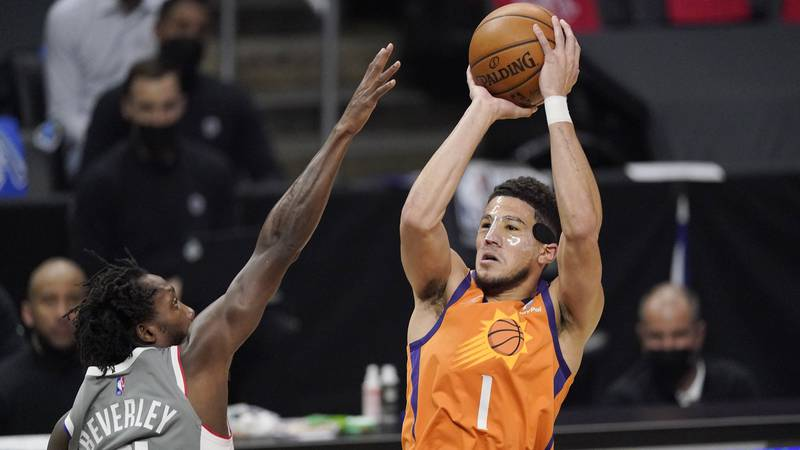 Phoenix Suns guard Devin Booker, right, shoots as Los Angeles Clippers guard Patrick Beverley...