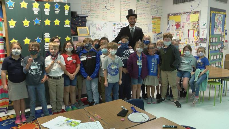Dr. John Strycker, dressed as Abraham Lincoln, poses for a picture with students on Friday.