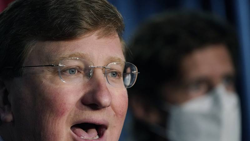 Mississippi Gov. Tate Reeves, responds to a reporter's question, left, as State Health Officer...