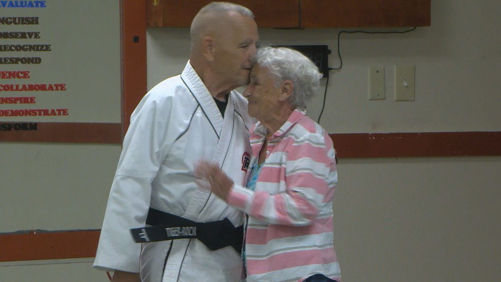 Tom Gustafson kisses his wife after she presented him with the black belt he earned.