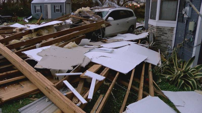 Debris from Anthony Kennedy Sr.'s roof covers the front yard and car at Nancy Patton's house on...