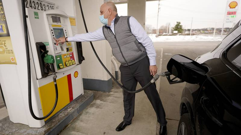 Jeremy Heskett, of Boston, prepares to pour gasoline at a Shell gas station, Thursday, Feb. 18,...