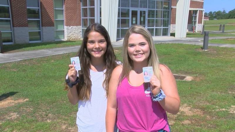 Two teens pose with their new permits after getting them on Saturday.