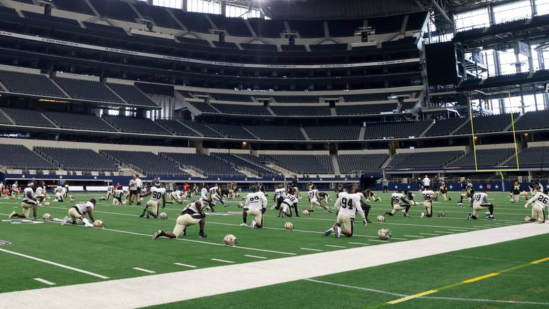 The New Orleans Saints stretch as they prepare for an NFL football workout at AT&T Stadium in...