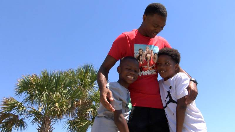Marcus Whitfield hugs his two sons on Father's Day. Whitfield, along with two other men, talked...